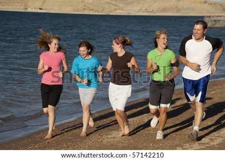 A mother and father laughing at each other, while they are exercising with their daughters. - stock photo