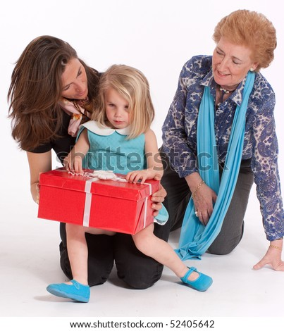 A mother and grandmother watching a little girl open a gift box - stock photo
