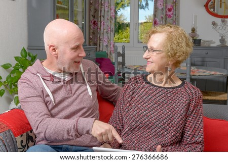 a mother and her adult son looking at a digital tablet - stock photo