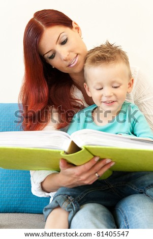 A Mother and her boy sitting on a couch reading a Book - stock photo