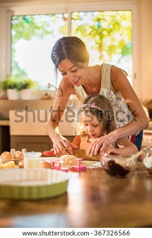 A mother and her four years old blonde daughter are cooking in a luminous kitchen. They are working on a pastry with a rolling pin on a wooden table full of ingredients and a green baking pan. - stock photo