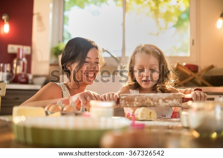 A mother and her four years old daughter are cooking in a luminous kitchen. They are working on a pasty with a rolling pin on a wooden table full of ingredients and a green baking pan. Shot with flare - stock photo