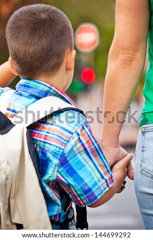 A mother and her little boy crossing the street on the way to school. - stock photo
