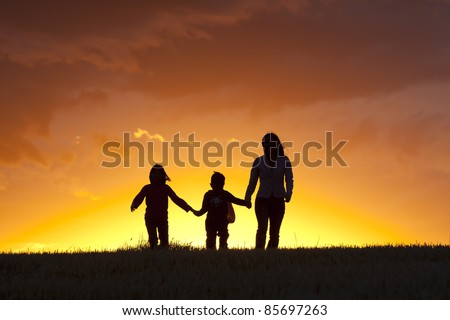 A mother and her two kids walk along into the sunset. - stock photo