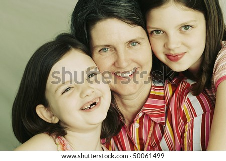 A mother and her two young daughters embrace and smile towards the camera. Horizontal shot - stock photo