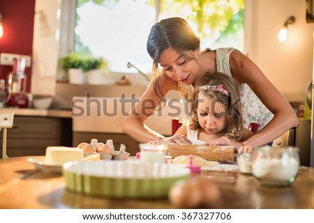 A mother and her 4 years old daughter are cooking in a luminous kitchen. They are working on a pastry with a rolling pin on a wooden table full of ingredients and a green baking pan. Shot with flare - stock photo