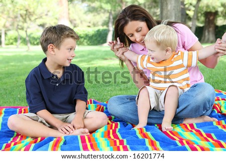 A mother and sons having fun while playing in the park - stock photo