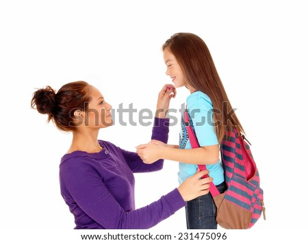 A mother getting her eight year old girl ready for school, the girl with a backpack, isolated on white background.  - stock photo