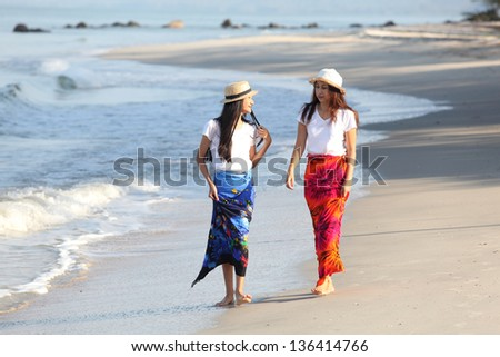 A mother having fun with her daughters on the beach - stock photo