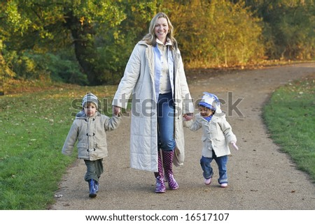 A mother, her son and daughter walking through a park filled with autumnal colors