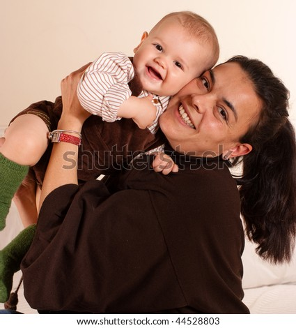 A mother  holding and cuddling her baby - stock photo