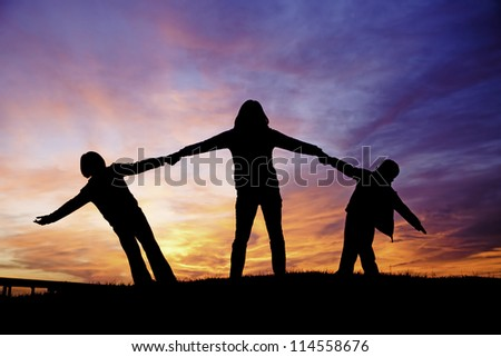 A mother holds her two children while playing during sunset. - stock photo