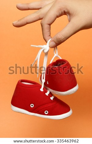 A mother holds on to a pair of baby shoes. - stock photo