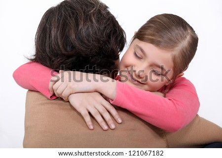 A mother hugging her daughter. - stock photo