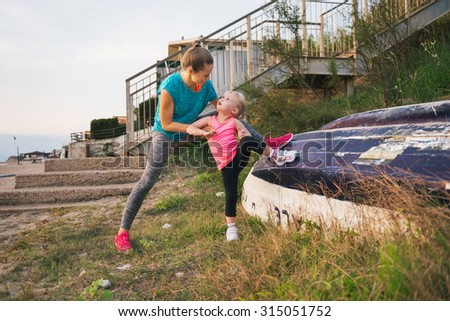 A mother in fitness gear is standing behind her daughter, guiding her in how to stretch out using an upturned boat. Happy and earnest, the little girl looks up at her mother lovingly. - stock photo