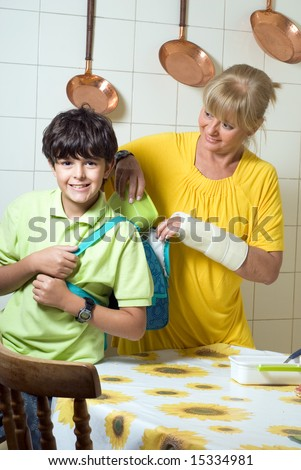 A mother is packing a lunch for her son in his backpack.  She is looking at him and he is looking at the camera.  Vertically framed shot. - stock photo