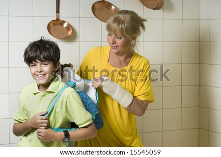 A mother is packing a lunch for her son in his backpack.  She is looking at him and he is looking at the camera.  Horizontally framed shot. - stock photo