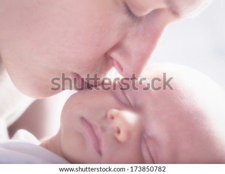 a mother kiss the beech of a new born sleaping baby. High key effect.  - stock photo