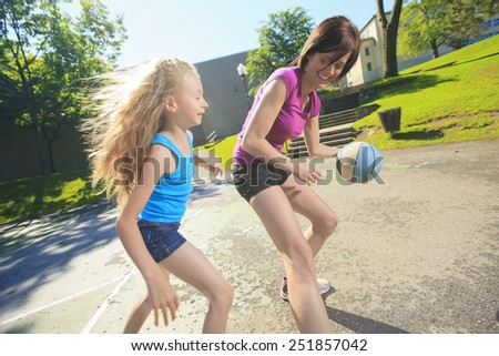 A mother play basketball with his daughter - stock photo
