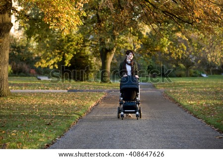 A mother pushing a stroller in the park - stock photo