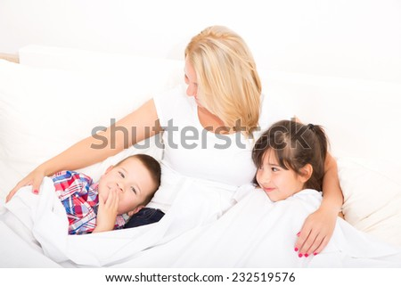 A mother relaxing in bed with her daughter and her son.  - stock photo