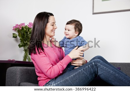 A mother sitting on a sofa holding her baby son  - stock photo