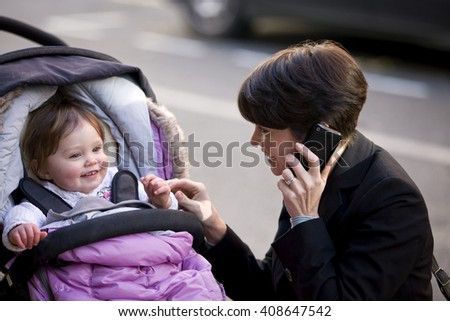 A mother smiling at her baby, talking on her mobile phone - stock photo