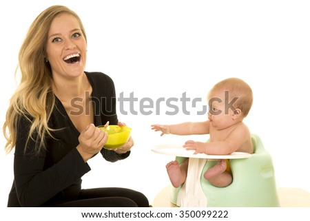 A mother with a big smile, laughing while her baby is reaching out for more food.
