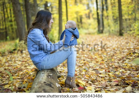 A Mother with daughter baby in autumn forest