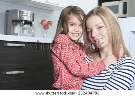 A Mother with daughter standing in kitchen. Interior portrait. - stock photo