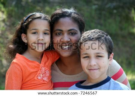 A mother with her young children of a mixed race family - stock photo