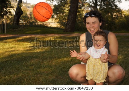 "A mother with nine month old daughter are playing ""catch the ball"" on a hot summer day."