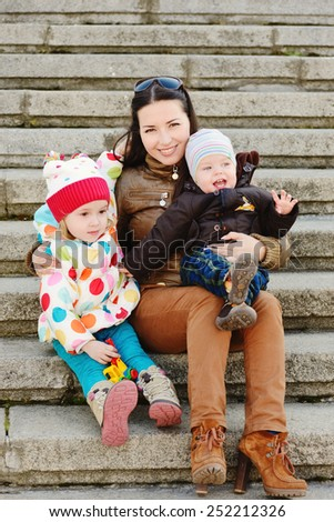 a mother with two little children outdoors - stock photo