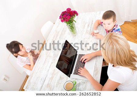 A mother working at home with a laptop and parenting her two children. - stock photo
