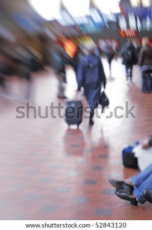 A motion and lens burred image of people traveling