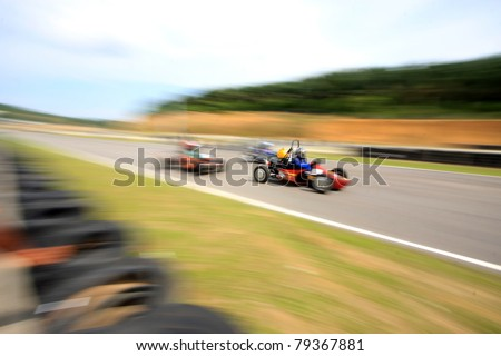 A motion blur of racing car overtaking - stock photo