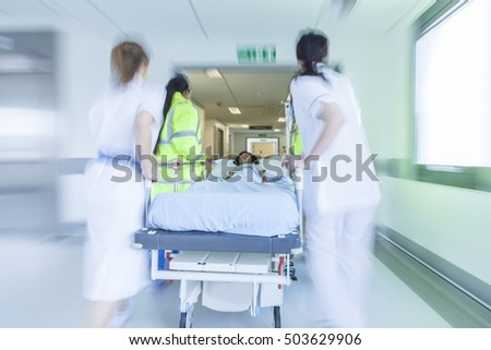 A motion blurred photograph of a child patient on stretcher or gurney being pushed at speed through a hospital corridor by doctors & nurses to an emergency room