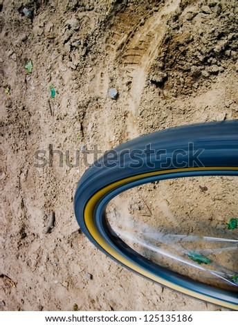 A motion blurred tire against some sandy ground. - stock photo