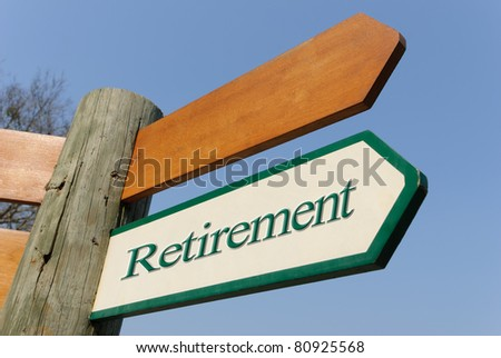 A motivational green and white wooden signpost pointing towards retirement  on sunny blue sky