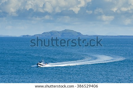 A motorboat approaches Tiree over the seas of the inner Hebrides on the westcoast of Scotland