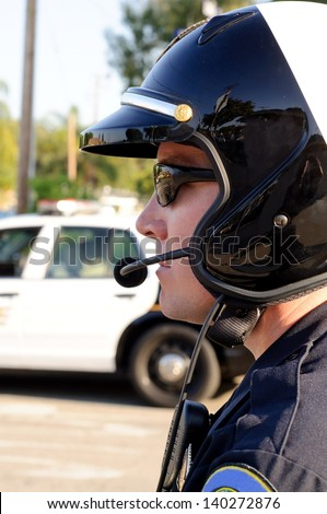 A motorcycle police officer watches traffic during his shift. - stock photo