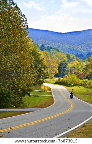 A motorcycle rider on a mountain highway surrounded by autumn colors. - stock photo