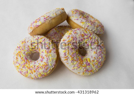 A mound of donuts. Crumpet for tea. Tasty food cakes. Delicious classic cakes: fried doughnuts glazed with caramel. Nutritious dish that promotes obesity. - stock photo
