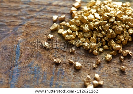 a mound of gold on a old wooden work table