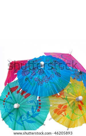 A mound of multicolored cocktail umbrellas isolated on white. - stock photo