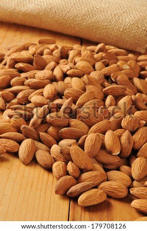 A mound of organic almonds on a wooden counter with burlap