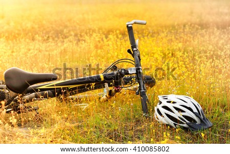 A mountain bike parked on a yellow grass flower field with a white helmet