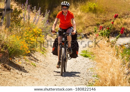 A mountain biker rides along a winding gravel track in a valley along the spring meadows of flowers