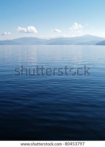 A Mountain Lake Under a Deep Blue Sky Coeur d'Alene Idaho USA - stock photo
