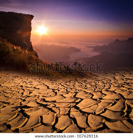 A mountain looks over a cracked earth landscape - stock photo